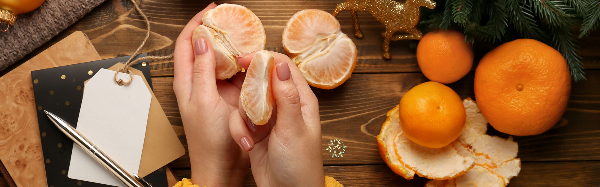 Peeling clementines among christmas decorations.